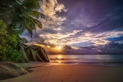 Sunset on paradise beach at anse georgette, praslin, seychelles. Picturesque sunset on dream beach at anse georgette on praslin on the seychelles. A big granite stock photography