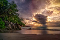 Sunset on paradise beach at anse georgette, praslin, seychelles 7. Sunbeams during sunset behind a big cloud at anse georgette on praslin on the seychelles royalty free stock photography