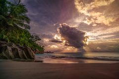 Sunset on paradise beach at anse georgette, praslin, seychelles 8. Sunbeams during sunset behind a big cloud at anse georgette on praslin on the seychelles royalty free stock photo