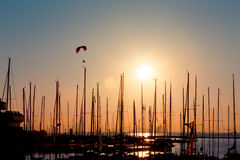 Sunset paragliding over yachts Stock Photo