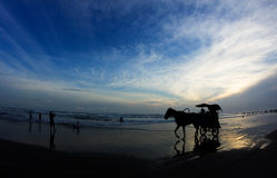 Sunset at Parangtritis Beach, Jogjakarta, Indonesia. Silhouettes of horse with a cart and people relaxing at Parangtritis Beach famous by its black sands Stock Photo
