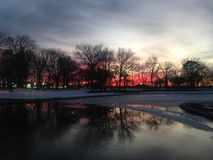 Sunset in a Park with Ice on Frozen Pond in Winter. Royalty Free Stock Photos