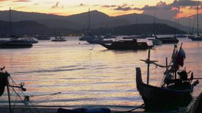 Sunset in the peaceful fishing port. Fishing boats anchored in a peaceful port at the sunset. 3840x2160, 4k. Twilight in the peaceful fishing port. Fishing boats stock footage