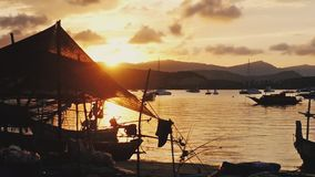 Sunset in the peaceful fishing port. Fishing boats anchored in a peaceful port at the sunset. 1920x1080. Twilight in the peaceful fishing port. Fishing boats stock video footage