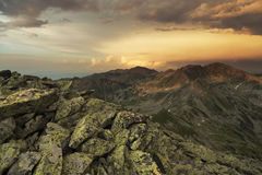Sunset on the peak of mountains. Beautiful sunset on the Bucura peak, with a colorfull sky and rocks in the foreground, at Retezat Mountains royalty free stock image