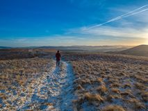 Late afternoon walk in the Pentlands. Sunset in the Pentlands, with a lone hiker some way off in the distance and the Lammermuir Hills in the background. Crisp Stock Image