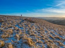 Late afternoon walk in the Pentlands. Sunset in the Pentlands, with a lone hiker some way off in the distance and the Lammermuir Hills in the background. Crisp Royalty Free Stock Photo