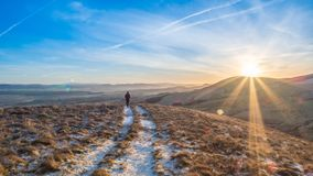 Late afternoon walk in the Pentlands. Sunset in the Pentlands, with a lone hiker some way off in the distance and the Lammermuir Hills in the background. Crisp Stock Images