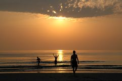 Sunset with people. Who are playing and swimming Royalty Free Stock Photos