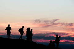 Sunset people's silhouettes on top of a hill Stock Photos