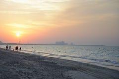 Sunset. People walking on the beach stock photos