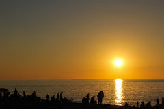 Sunset and people. Wonderful sunset over the sea in bright colors Royalty Free Stock Photo