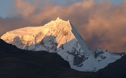 Sunset in the Peruvian Andes. Sunset shines over a snowy mountain peak in Northern Peru. The clouds pass behind as the golden glow fades royalty free stock photos