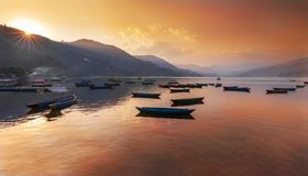 Sunset in Phewa Lake and reflection of sky on the water. Pokhara Nepal stock photo