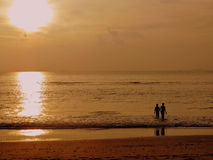 Sunset photo of a boy and girl walking into the sea while their reflection is cast on the beach behind them. Stock Images