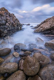 Sunset photograph of misty waves. Crashing on the rocks by the South Coast in South Africa Stock Images