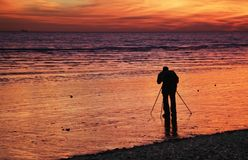 Sunset Photographer. Photographer with tripod (silhouette) takes pictures of sunset Royalty Free Stock Photo