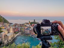 Sunset photography on tripod. Hand pushing the button of a camera on a tripod to catch a sunset shot of Vernazza, Cinque Terre, Liguria, Italy. UNESCO World Royalty Free Stock Image