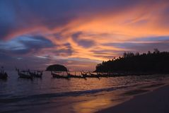 Sunset on Phuket beach, Thailand. Sunset on Kata beach in Phuket, Thailand with fishing boats in foreground Stock Photos