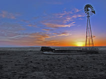 Sunset with pickup and windmill on plains. Stock Photo