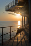 Sunset pier along coast Stock Image