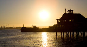 Sunset pier at the beach. A sunset over the water overlooking a pier at a local beach Stock Photos