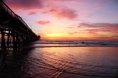 Sunset at a pier with cotton candy clouds. In California royalty free stock image