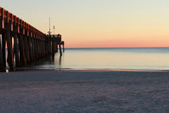 Sunset At The Pier. The last of the golden hour on the sand by the pier at the beach Stock Photography