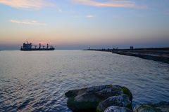 Sunset at pier and a passing ship Royalty Free Stock Images