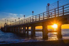 Sunset through pier. Pressing in the sea Stock Image