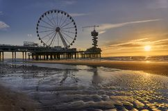 Sunset at The Pier in Scheveningen with waterreflection royalty free stock images