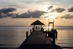 Sunset and Pier in Tropical Lagoon Royalty Free Stock Image