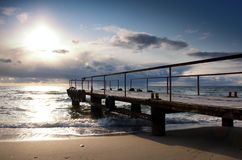 Sunset on the pier. Waves are washing the sand at the sunset pier Stock Image