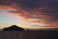 Sunset with pink sky, island and iceberg silhouette stock photo
