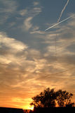 Sunset with planes. Cloud,clouds,color,colorful,colour, yellow,orange,glow, glowing, red, skies, sky, sunset, sunsets, twilight,sun,tree,leaves Royalty Free Stock Images