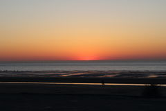 A sunset plunging into the cloudless  Sea On the beach of dunkerque Stock Photo