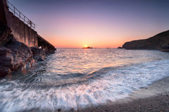 Sunset at Polpeor Cove in Cornwall Stock Image