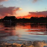 Sunset Pond. As the sun sets on a pond, the sky lights up red, orange, and pink Stock Photography