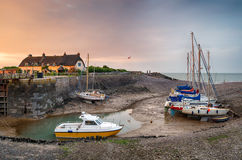 Sunset at Porlock Weir. Cottages and boats on the harbour at Porlock Weir on the Somerset coast royalty free stock photo