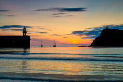 Sunset at Port Erin in the Isle of Man. Sunset over Port Erin bay in the Isle of Man, with the harbor and Bradda Head and Milner's Tower stock photo
