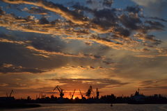 Sunset at the port. Of Kherson. Construction cranes against the setting sun Stock Image