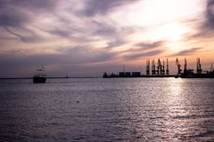 Sunset in the port. the ship goes to sea. Seaport in the sunset rays of the sun. ship on the horizon at sunset stock images