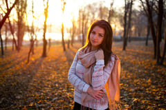 Sunset portrait of beautiful brunette young woman in autumn park Stock Photo