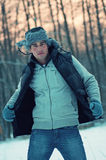 Sunset portrait of a handsome young man in winter. Fashion sunset portrait of a posing handsome young man in his jacket in winter forest Stock Photo