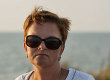 Sunset portrait of tanned middle age woman in sunglasses Stock Photo
