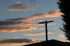 Sunset power lines. Power lines running to a rural building with sunset sky background, framed by tree on the right stock images