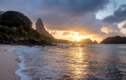 Sunset at Praia do Cachorro Beach with Morro do Pico on background - Fernando de Noronha, Pernambuco, Brazil. Sunset at Praia do Cachorro Beach with Morro do stock images