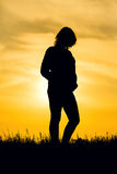 Sunset and pregnant. Silhouette pregnant woman on sunset background stock image