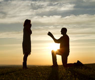 Sunset Proposal. Male making a marriage proposal against the backdrop of the setting sun royalty free stock image
