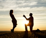 Sunset Proposal. Male making a marriage proposal against the backdrop of the setting sun royalty free stock photos